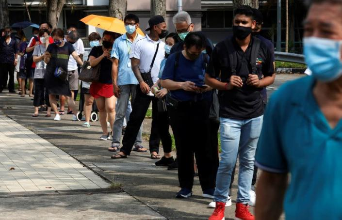 People queue up outside a quick test centre to take their coronavirus disease (COVID-19) antigen rapid tests, in Singapore