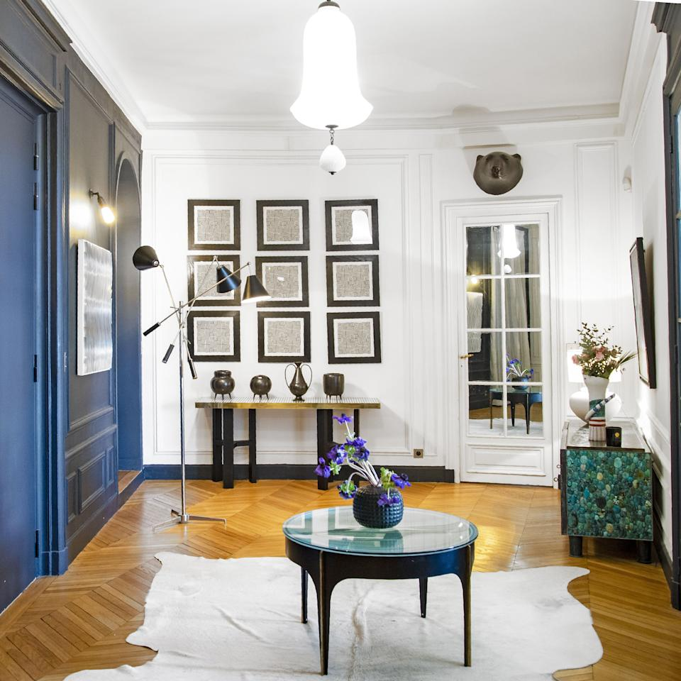"""<div class=""""caption""""> The opaline glass lantern in the entrance hall is Murano from the 1950s. The standing lamp is called Triennale by Angelo Lelli for <a href=""""http://www.arredoluce.com/en/"""" rel=""""nofollow noopener"""" target=""""_blank"""" data-ylk=""""slk:Arredoluce"""" class=""""link rapid-noclick-resp"""">Arredoluce</a>. A resin console by designer Etienne Allemeersch from 1970 supports a collection of Gio Ponti ceramics. On the wall are ink works by Argentinian film director David Lipszyc from circa 1970. To the right is a cabinet by Kam Tin with turquoise and patinated brass. In the foreground is a table by French artist and designer Max Ingrand for Fontana Arte circa 1960. </div>"""