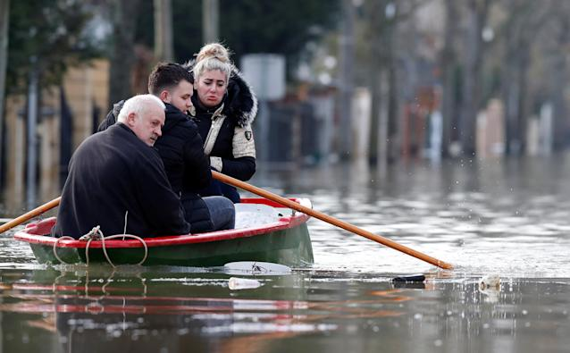 <p>Residents on a small boat leave home in a flooded street of Villeneuve-Saint-Georges, near Paris, France, Jan. 26, 2018. (Photo: Christian Hartmann/Reuters) </p>
