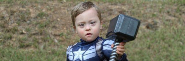 Adam's son dressed as Captain America holding Thor's hammer.