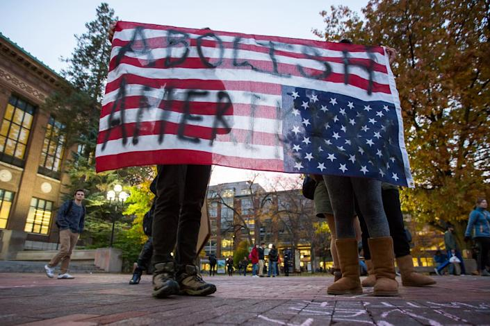 """<p>Two people hold an American Flag upside down, which reads, """"Abolish Amerikkka"""" during an anti-Trump rally at the Diag on the University of Michigan's campus on Wednesday, Nov. 9, 2016. Later in the evening about 1,00 people gathered at the Diag for a gathering promoting love, equality, and surprise of the recent election of Donald Trump. (Matt Weigand/The Ann Arbor News via AP) </p>"""