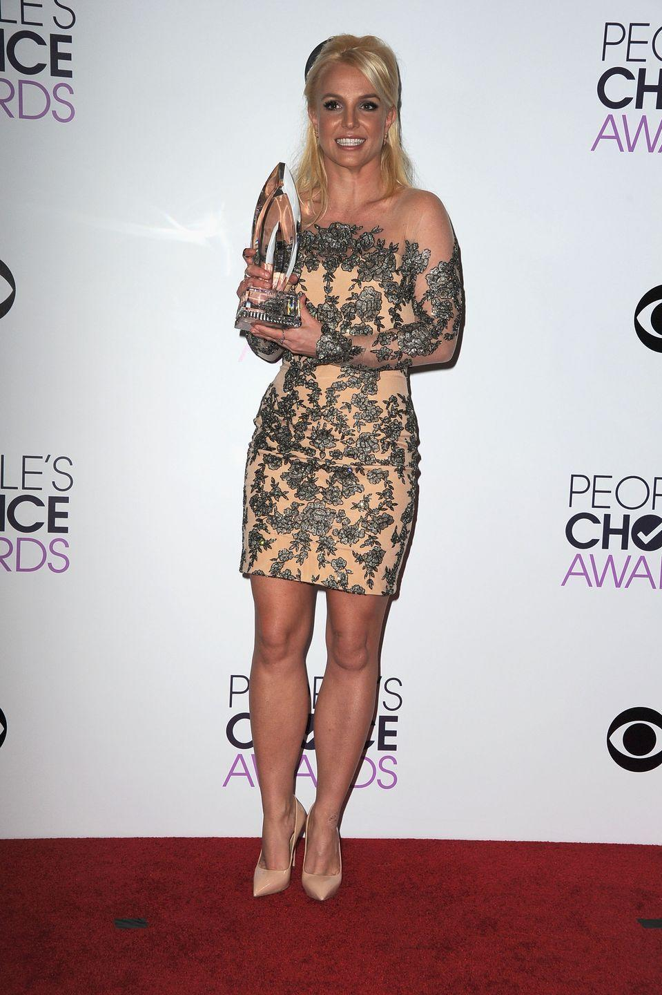 <p>The pop star poses with her People's Choice Award on the red carpet in an embellished mini with an illusion neckline. </p>