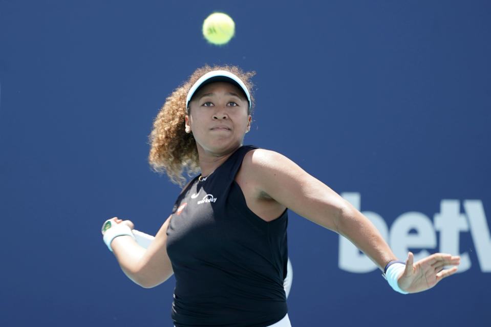Naomi Osaka of Japan returns to Ajla Tomljanovic of Australia during the Miami Open tennis tournament, Friday, March 26, 2021, in Miami Gardens, Fla. (AP Photo/Marta Lavandier)