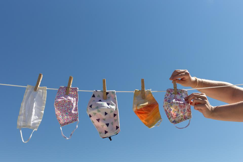 Woman hands stretching reusable cloth face masks on a clothesline