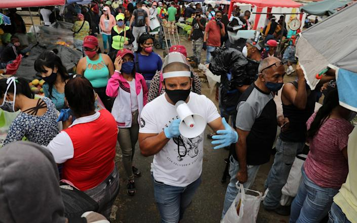 Walter Rivera, director of the Coche wholesale market, shouts the rules around Covid-19 precautions at shoppers and sellers in Caracas - Reuters
