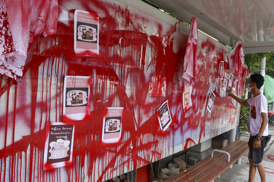 "An anti-coup protester uses red paint as he writes slogans at a bus stop on Wednesday April 14, 2021 in Yangon, Myanmar. Anti-coup protesters kept public demonstrations going despite the threat of lethal violence from security forces. The words reads ""We do not accept military coup"". (AP Photo)"