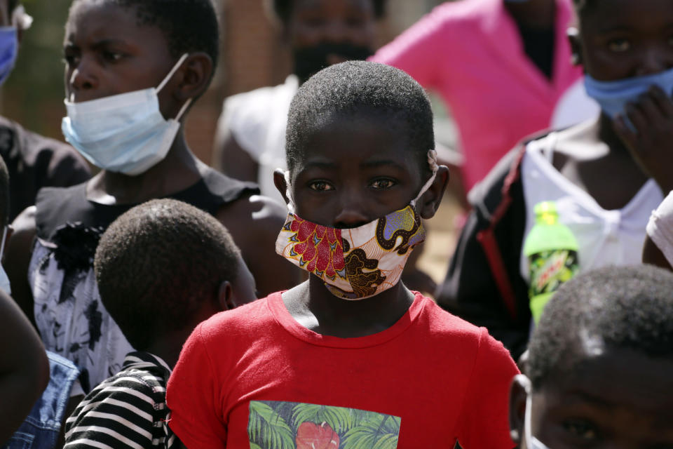A young boy wears a face mask while attending a social event in Epworth, Harare, Friday, June, 11, 2021. Zimbabwe has opened up COVID-19 vaccination to the majority of teen children, while also allowing fully vaccinated people to eat in restaurants as a devastating third wave recedes and previously hesitant people take up jabs in higher numbers.(AP Photo/Tsvangirayi Mukwazhi)