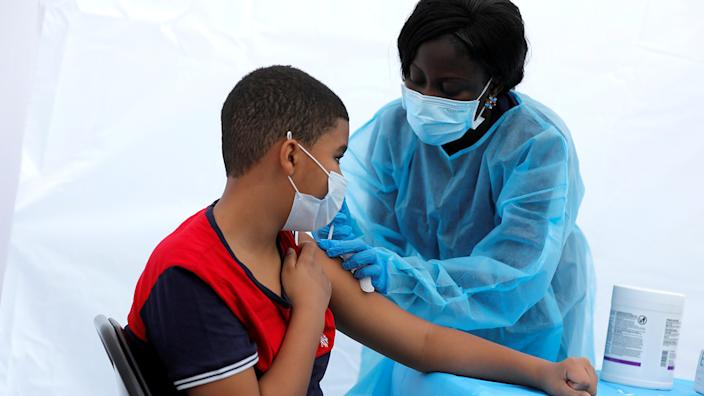 12-year-old Justing Concepcion receives a dose of the Pfizer-BioNTech vaccine for the coronavirus disease (COVID-19) from registered nurse Angela Nyarko, during a vaccination event for local adolescents and adults outside the Bronx Writing Academy school in the Bronx borough of New York City, New York, U.S., June 4, 2021. (Mike Segar/Reuters)