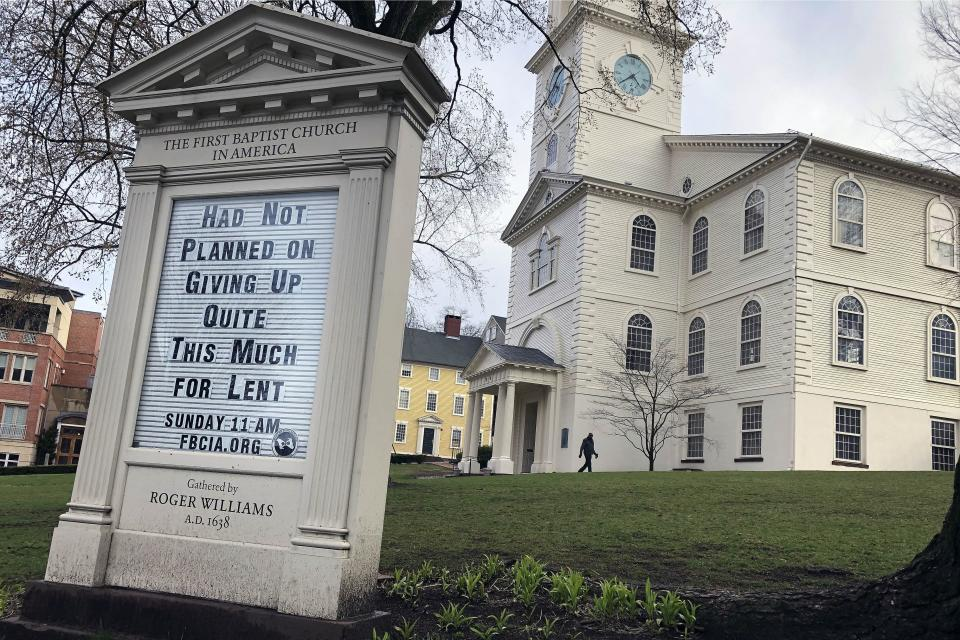 In this March 24, 2020, photo, a man walks past the First Baptist Church in America in Providence, R.I. Americans are turning to humor in many forms, like the sign in front of the church, as they cope with the fear and anxiety the coronavirus pandemic has unleashed. (AP Photo/William J. Kole)