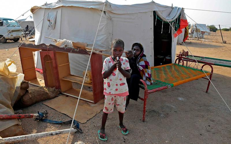 Displaced children stand outside a tent a shelter camp in the village of Tamaniyet, north of Sudan's capital Khartoum - Mazen Mahdi/ AFP