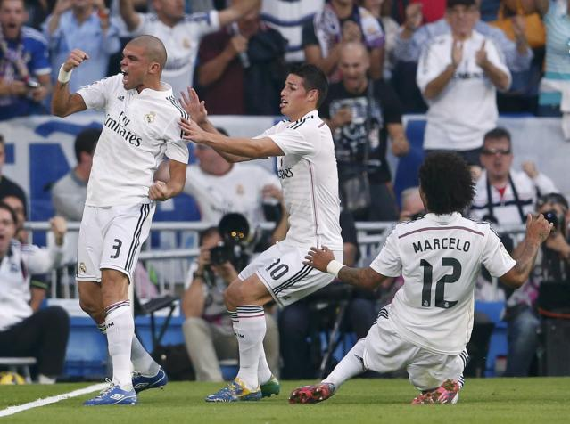 "Real Madrid's Pepe (L) celebrates with James Rodriguez (C) and Marcelo after scoring against Barcelona during their Spanish first division ""Clasico"" soccer match at the Santiago Bernabeu stadium in Madrid October 25, 2014. REUTERS/Juan Medina (SPAIN - Tags: SOCCER SPORT)"