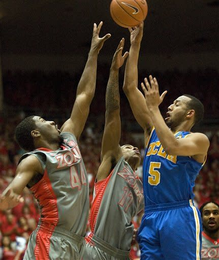 UCLA's Jerime Anderson (5) tries to shoot over the defense of Arizona's Solomon Hill (44) and Josiah Turner (11) during the first half of an NCAA college basketball game at McKale Center in Tucson, Ariz., Saturday, Feb. 25, 2012. (AP Photo/Wily Low)