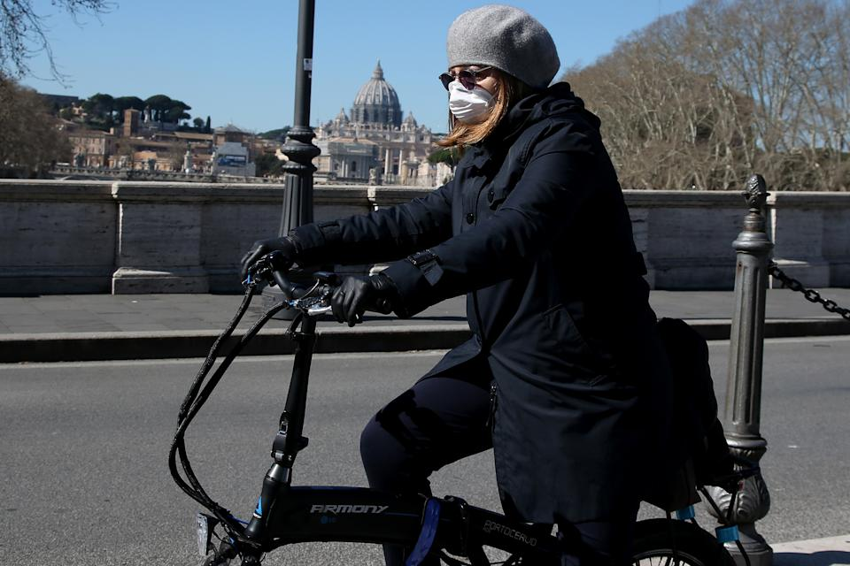 ROME, ITALY - MARCH 11: A girl wearing a protective mask crosses a bridge by bicycle in front St. Peter's Basilica on March 11, 2020 in Rome, Italy. The Italian Government has taken the unprecedented measure of a nationwide lockdown in an effort to fight the world's second-most deadly coronavirus outbreak outside of China. The movements in and out are allowed only for work and health reasons proven by a medical certificate. The justifications for the movements needs to be certified with a self-declaration by filling in forms provided by the police forces in charge of the checks. (Photo by Franco Origlia/Getty Images)