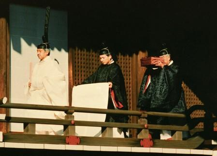 FILE PHOTO: Emperor Akihito walks ahead of priests prior to ceremonies marking his accession to Japan's Chrysanthemum Throne