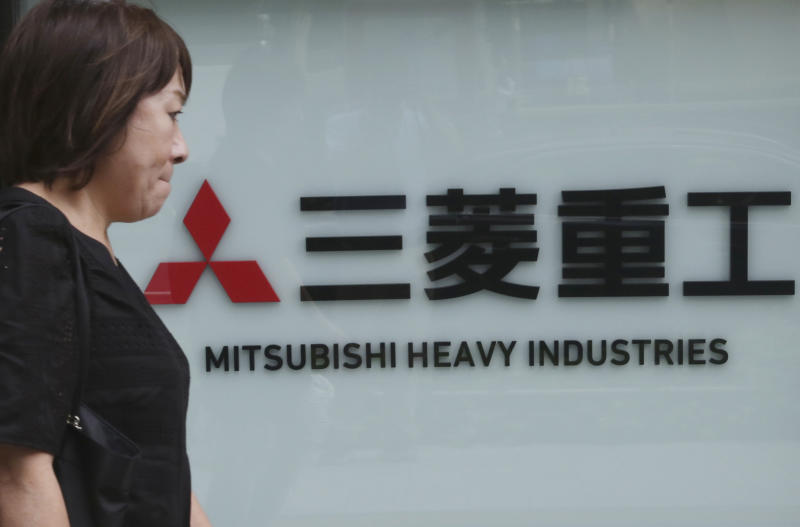 A woman walks past the company sign of the Mitsubishi Heavy Industries in Tokyo, Tuesday, July 23, 2019. Colonial-era Korean laborers have formally registered their request with a South Korean court to get its approval for the sale of local assets of their former Japanese employer. (AP Photo/Koji Sasahara)