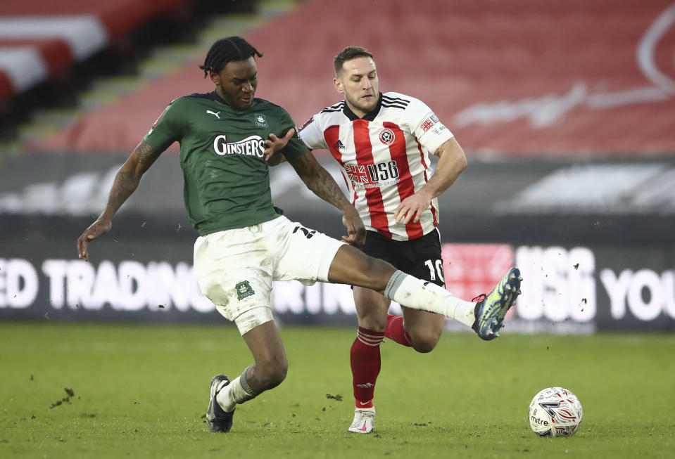 Plymouth Argyle's Jerome Opoku, left, and Sheffield United's Billy Sharp battle for the ball during the English FA Cup fourth round soccer match at Bramall Lane, Sheffield, England, Saturday Jan. 23, 2021. (Tim Goode/PA via AP)