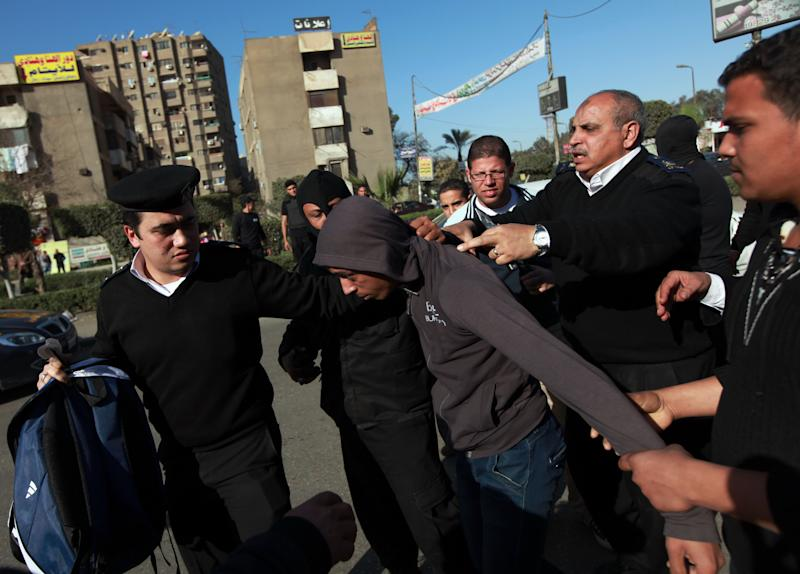 FILE - In this Friday, Jan, 24, 2014 file photo, Egyptian security forces detain one of the supporters for ousted President Mohammed Morsi as they protest in Cairo's Nasr City district, Egypt. On Tuesday, Feb. 11, 2014, the third anniversary of the day Hosni Mubarak stepped down as Egypt's president after an 18-day uprising, the government blocked access to Tahrir Square and letters emerged from activists reporting that they have been beaten and subjected to other abuses by police after being arrested in a string of protests in late January. (AP Photos/El Shorouk newspaper, Sabry Khaled, File) EGYPT OUT