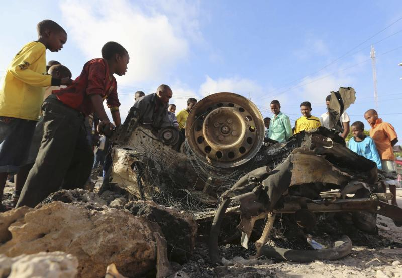Somali children crowd around wreckage of car that exploded in front of City Palace hotel on Friday night, leaving one injured, in Mogadishu