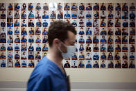 A member of staff passes in front of a collection of portraits of medical staff at Bichat Hospital, AP-HP, in Paris, Thursday, April 22, 2021. France still had nearly 6,000 critically ill patients in ICUs this week as the government embarked on the perilous process of gingerly easing the country out of its latest lockdown, too prematurely for those on pandemic frontlines in hospitals. President Emmanuel Macron's decision to reopen elementary schools on Monday and allow people to move about more freely again in May, even though ICU numbers have remained stubbornly higher than at any point since the pandemic's catastrophic first wave, marks another shift in multiple European capitals away from prioritizing hospitals. (AP Photo/Lewis Joly)
