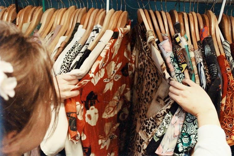 Woman looking at blouses on a clothing rack