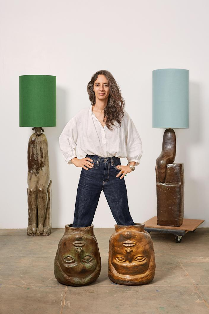 """D'Appolonio posing with two of her ceramic """"pot heads"""" playfully worn as boots."""