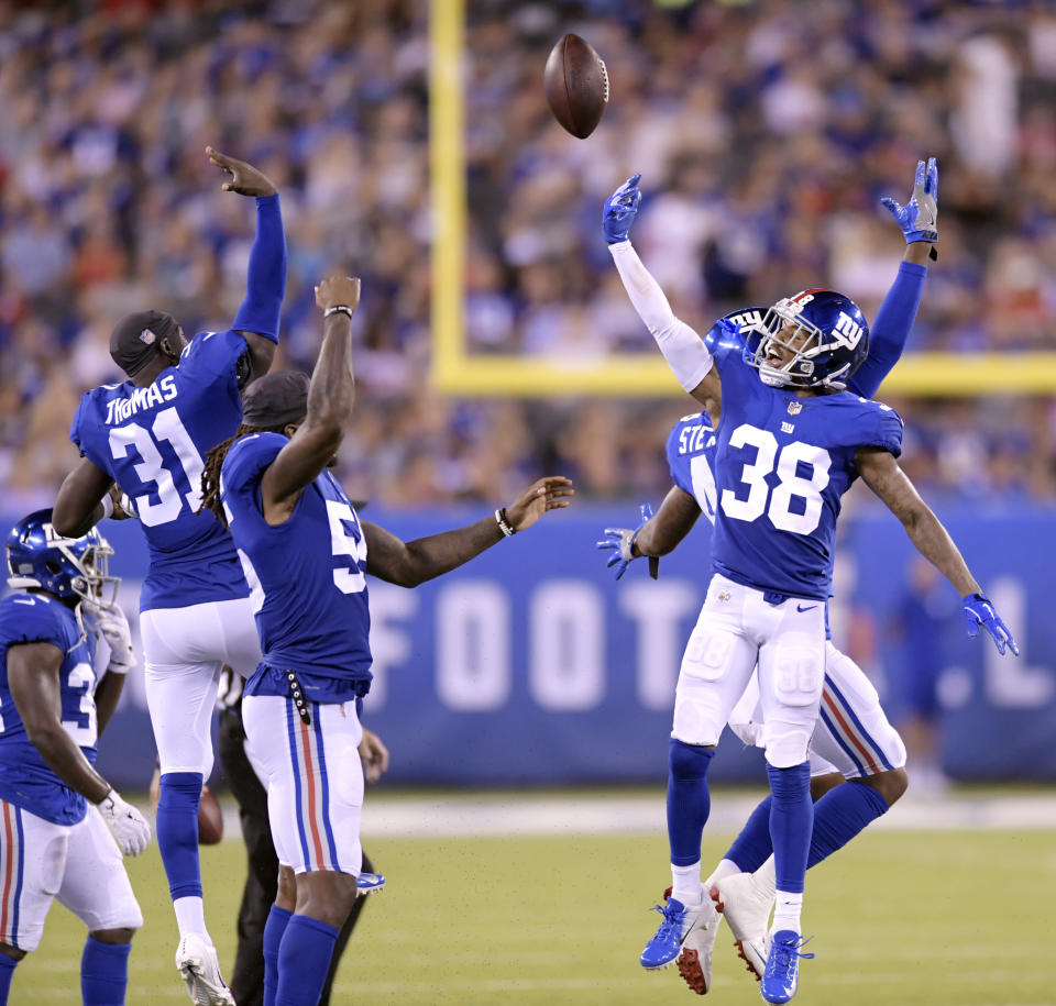New York Giants cornerback Donte' Deayon (38) celebrates with teammates after catching his second interception on passes from New England Patriots quarterback Danny Etling, not pictured, during the first half of an NFL preseason football game, Thursday, Aug. 30, 2018, in East Rutherford. (AP Photo/Bill Kostroun)