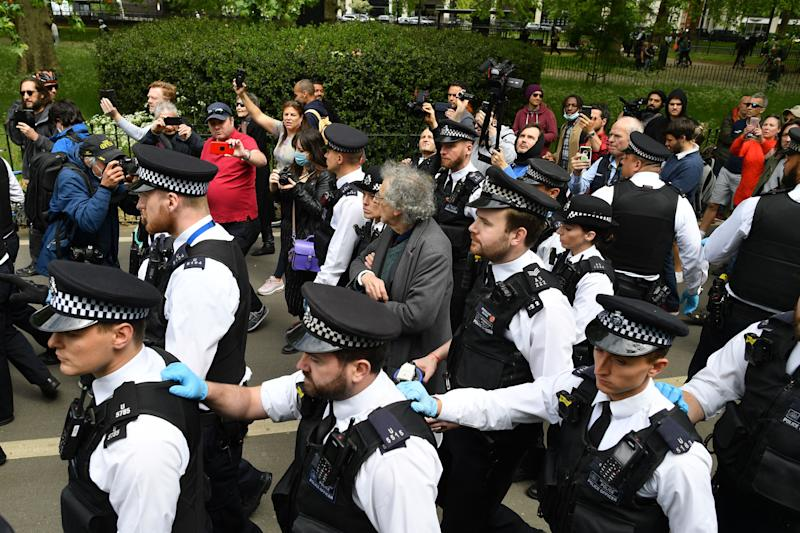 "Piers Corbyn (C), brother of former Labour Party leader Jeremy Corbyn, is led away by police officers at an anti-coronavirus lockdown demonstration in Hyde Park in London on May 16, 2020, following an easing of lockdown rules in England during the novel coronavirus COVID-19 pandemic. - Fliers advertising 'mass gatherings' organised by the UK Freedom Movement to oppose the government lockdown measures and guidelines put in place to halt the spread of coronavirus in parks around the UK calling for attendees to bring a picnic and music have been circulating on social media. People are being asked to ""think carefully"" before visiting national parks and beaches on the first weekend since coronavirus lockdown measures were partially eased in England. (Photo by JUSTIN TALLIS / AFP) (Photo by JUSTIN TALLIS/AFP via Getty Images)"