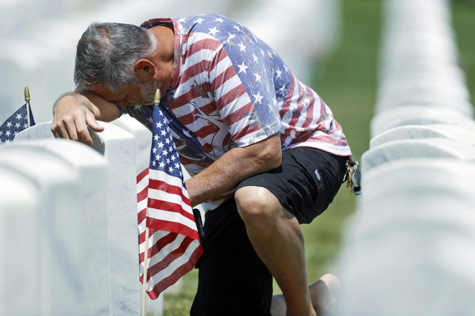 J.D. Madrid pauses for a moment at the grave of his father-in-law, Michael McBrien, in Fort Logan National Cemetery, Saturday, May 23, 2020, in Sheridan, Colo. Both Madrid and his father-in-law served in the U.S. Navy. While traditional events such as placing flags at the foot of gravestones for service members and ceremonies to mark Memorial Day were cancelled because of coronavirus concerns, survivors came out in force to offer their own tributes. (AP Photo/David Zalubowski)