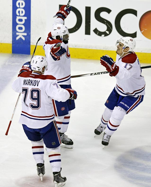 Montreal Canadiens defenseman P.K. Subban, center, raises his arms after scoring the game-winning goal off Boston Bruins goalie Tuukka Rask during the second overtime period of Game 1 in the second round of the Stanley Cup playoffs in Boston, Thursday, May 1, 2014. The Canadiens won 4-3. At left is defenseman Andrei Markov and at right is left wing Rene Bourque. (AP Photo/Charles Krupa)