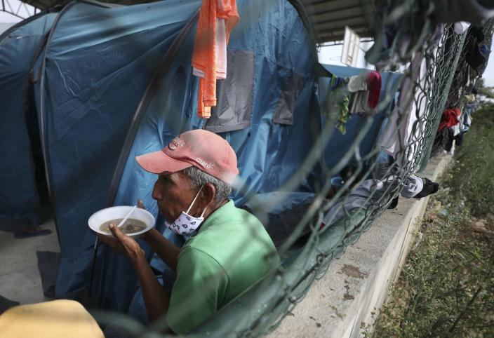 A Venezuelan sheltering at a community center gets a meal in Arauquita, Colombia, Thursday, March 25, 2021, on the border with Venezuela. Thousands of Venezuelans are seeking shelter in Colombia this week following clashes between Venezuela's military and a Colombian armed group in a community along the nations' shared border. (AP Photo/Fernando Vergara)