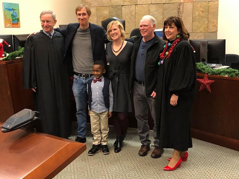 The Michigan boy (front centre) standing with adoptive parents David Eaton and Andrea Melvin, and the judges of Kent County Court with another man.