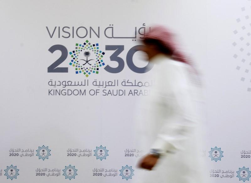 A Saudi man walks past the logo of Vision 2030 after a news conference in Jeddah