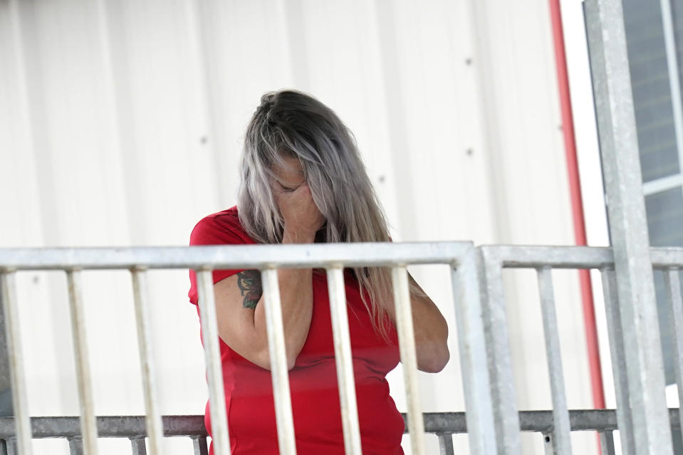 Marion Cuyler, fiancée of missing crew member Chaz Morales, talks on her cell phone at a fire station where family members of 12 people missing from a capsized oil industry vessel have been gathering, Thursday, April 15, 2021, in Port Fourchon, La. The lift boat capsized in the Gulf of Mexico during a storm on Tuesday, killing one with 12 others still missing. (AP Photo/Gerald Herbert)