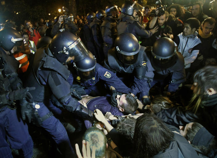 """File - In this Sept. 26, 2012 file photo, police clash with protestors during a demonstration at the parliament against austerity measures announced by the Spanish government in Madrid. Spain's government said Friday Oct. 19, 2012 it is considering a ban on photographing, filming and reproducing images of police and state security forces while """"in the exercise of their functions."""" Deputy Prime Minister Soraya Saenz de Santamaria said that after months of television and internet viewing of sometimes violent clashes between police and demonstrators a balance had to be struck """"between citizens' right to protest"""" and a need """"to uphold the integrity of state security forces."""" (AP Photo/Andres Kudacki, File)"""