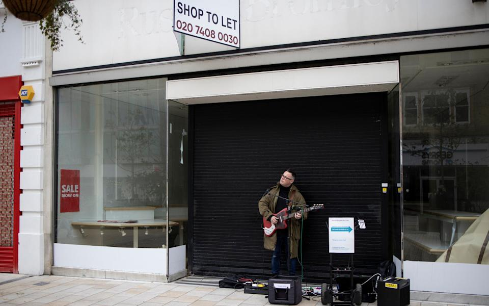 A busker outside a closed down shop on Bromley High Street - Getty