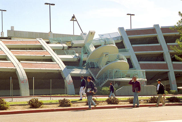 FILE - This Feb. 14, 1994 file photo shows California State University, Northridge students walking past a parking structure at the Los Angeles campus that collapsed in the Jan. 17 earthquake. Twenty-five years ago this week, a violent, pre-dawn earthquake shook Los Angeles from its sleep, and sunrise revealed widespread devastation, with dozens killed and $25 billion in damage. (AP Photo/Mark J. Terrill, File)