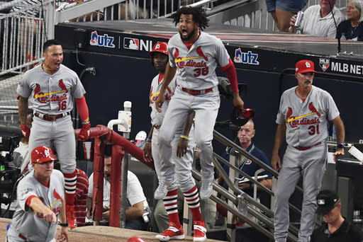 St. Louis Cardinals players celebrate St. Louis Cardinals Marcell Ozuna hit of a two RBI double in the ninth inning during Game 1 of a best-of-five National League Division Series against the Atlanta Braves, Thursday, Oct. 3, 2019, in Atlanta. (AP Photo/Scott Cunningham)