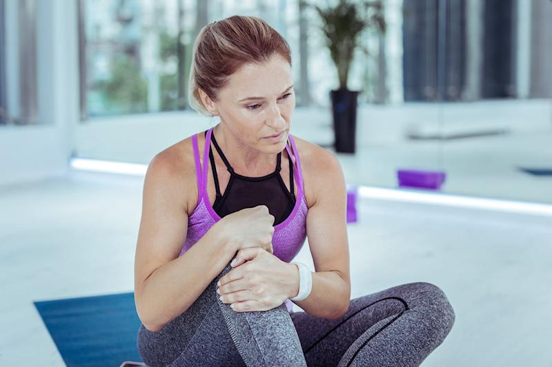 Woman holding knee in gym