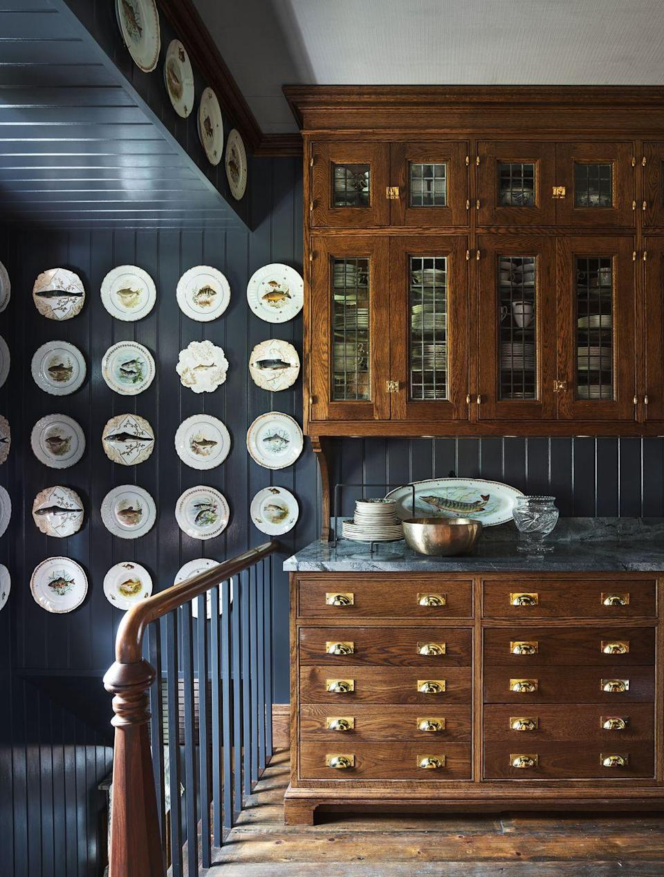 """<p>In designer Philip Mitchell's Nova Scotia home, the servery features vertical v-groove paneling as the backsplash. Heirloom Limoges fish sets hang on the painted paneled walls. Wall color, Gray by <a href=""""https://www.benjaminmoore.com/"""" rel=""""nofollow noopener"""" target=""""_blank"""" data-ylk=""""slk:Benjamin Moore"""" class=""""link rapid-noclick-resp"""">Benjamin Moore</a>.</p>"""