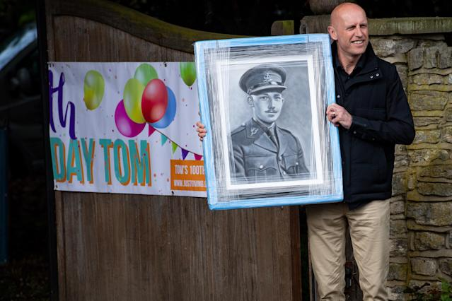 A man delivers a gift to the home of Captain Tom Moore in Bedford as he celebrates his 100th birthday. (PA)