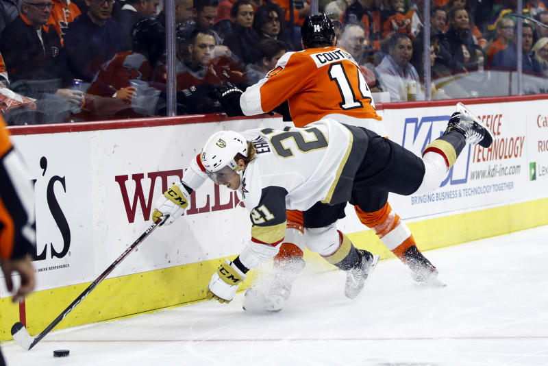 Vegas Golden Knights' Cody Eakin (21) dives for the puck past Philadelphia Flyers' Sean Couturier during the second period of an NHL hockey game Monday, Oct. 21, 2019, in Philadelphia. (AP Photo/Matt Rourke)