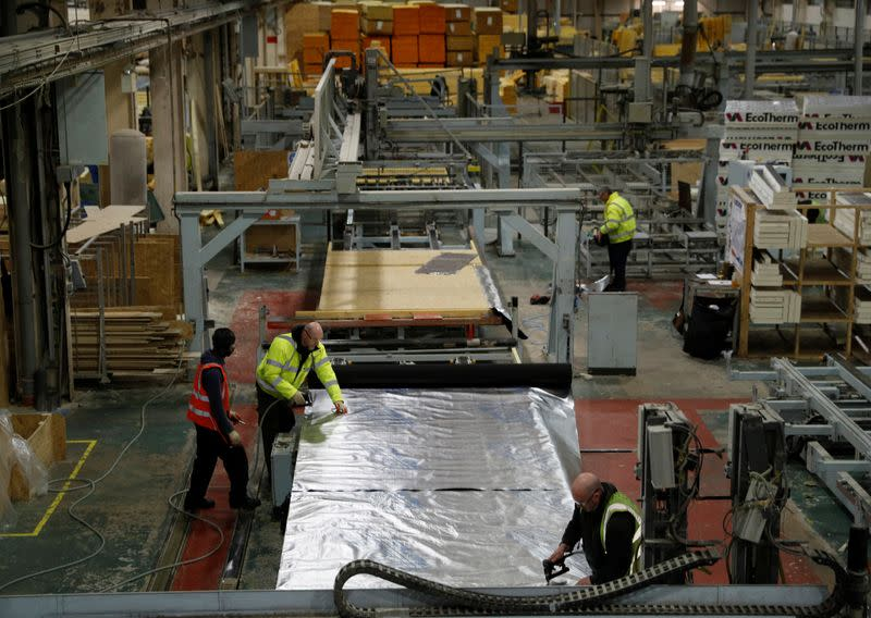 FILE PHOTO: Workers construct timber frame wall sections for a modular Space4 home produced by Persimmon in Birmingham