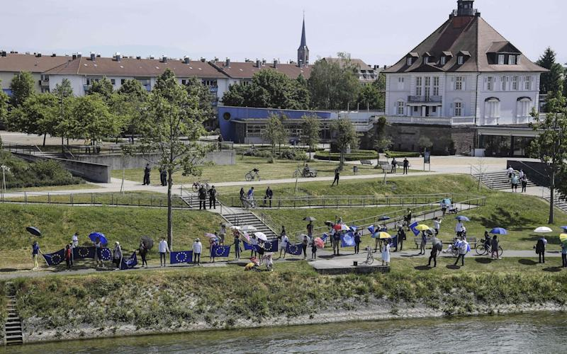 This picture taken on May 9, 2020 from the French side of the Europe Bridge in Strasbourg shows few dozens of Pro-European Union activists waving EU flags on the German side of the Rhine river as they mark Europe Day and protest against the closing of the borders between France and Germany as a results of the two countries' measures to stop the spread of the COVID-19 pandemic caused by the novel coronavirus. (Photo by FREDERICK FLORIN / AFP) (Photo by FREDERICK FLORIN/AFP via Getty Images) - FREDERICK FLORIN/AFP