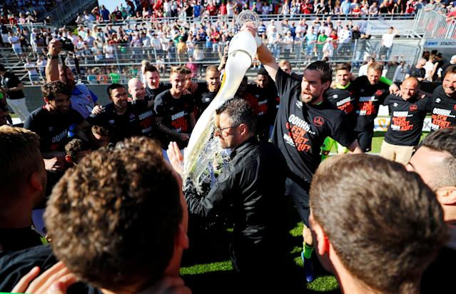 Soccer Football - 2. Bundesliga - SV Sandhausen v Nuremberg - BWT-Stadion am Hardtwald, Sandhausen, Germany - May 6, 2018 Nuremberg coach Michael Kollner celebrates promotion after the match with players and staff REUTERS/Kai Pfaffenbach DFL RULES TO LIMIT THE ONLINE USAGE DURING MATCH TIME TO 15 PICTURES PER GAME. IMAGE SEQUENCES TO SIMULATE VIDEO IS NOT ALLOWED AT ANY TIME. FOR FURTHER QUERIES PLEASE CONTACT DFL DIRECTLY AT + 49 69 650050 TPX IMAGES OF THE DAY