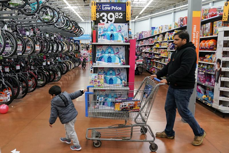 A boy and his father walk through the toy section of Walmart on Black Friday, a day that kicks off the holiday shopping season, in King of Prussia, Pennsylvania, U.S., on November 29, 2019. REUTERS/Sarah Silbiger.