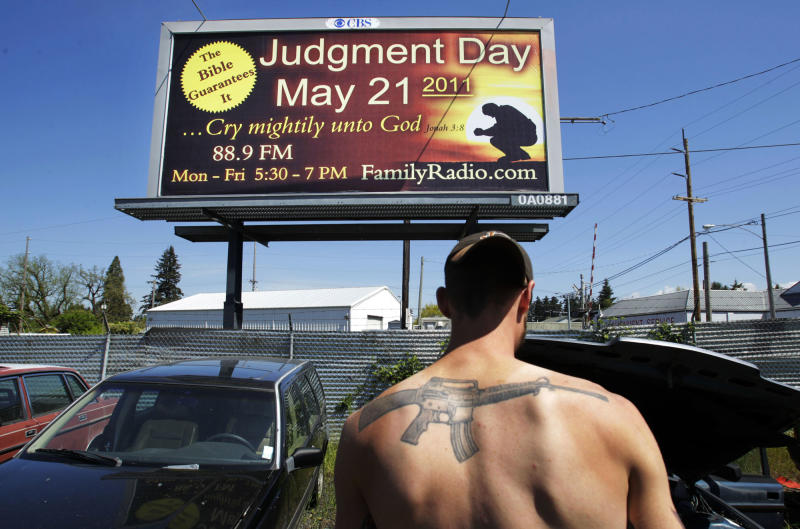 """FILE - In this Thursday, May 19, 2011 file photo, Mose Macdonald works in the impound yard of Stealth Recovery and Towing in Eugene, Ore. near a billboard proclaiming the upcoming Saturday, May 21, 2011 as """"Judgement Day."""" An organization run by Harold Camping of Oakland, Calif. has purchased billboards all over the country proclaiming May 21 will mark the end of the world. Camping, who used his evangelical ministry and thousands of billboards to broadcast the end of the world and then gave up public prophecy when his date-specific doomsdays did not come to pass, has died at age 92. Camping died at his home Sunday, Dec. 15, 2013 according to Family Radio Network marketing manager Nina Romero. She said he had been hospitalized after falling. (AP Photo/The Register-Guard, Chris Pietsch)"""