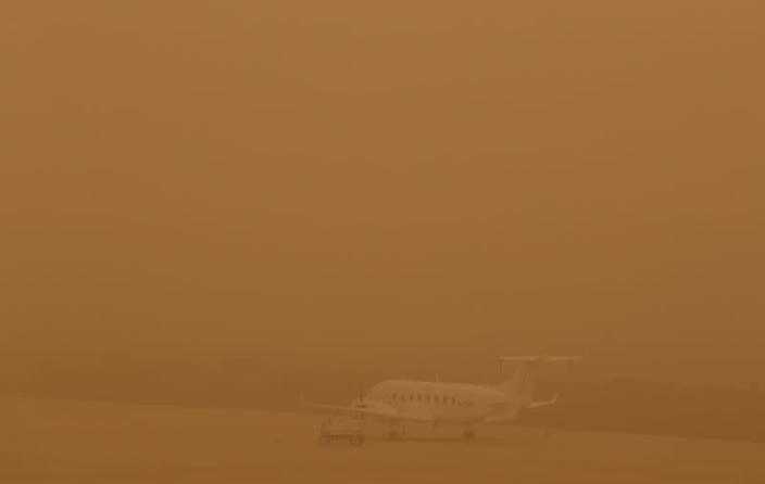 """A plane is seen parked on a tarmac during a sandstorm blown over from North Africa known as """"calima"""" at Las Palmas Airport"""