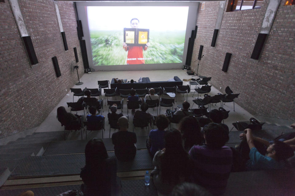 People watch a documentary film about Qian Yunhui, who died fighting for better compensation for seized land, at the Beijing Independent Film Festival in Beijing, China, Friday, Aug. 30, 2013. Chinese authorities have disrupted an independent film school, shut down two film festivals and harassed organizers of a third in recent months, say independent filmmakers, who see the moves as part of a general clampdown on freedom of expression. (AP Photo/Alexander F. Yuan)