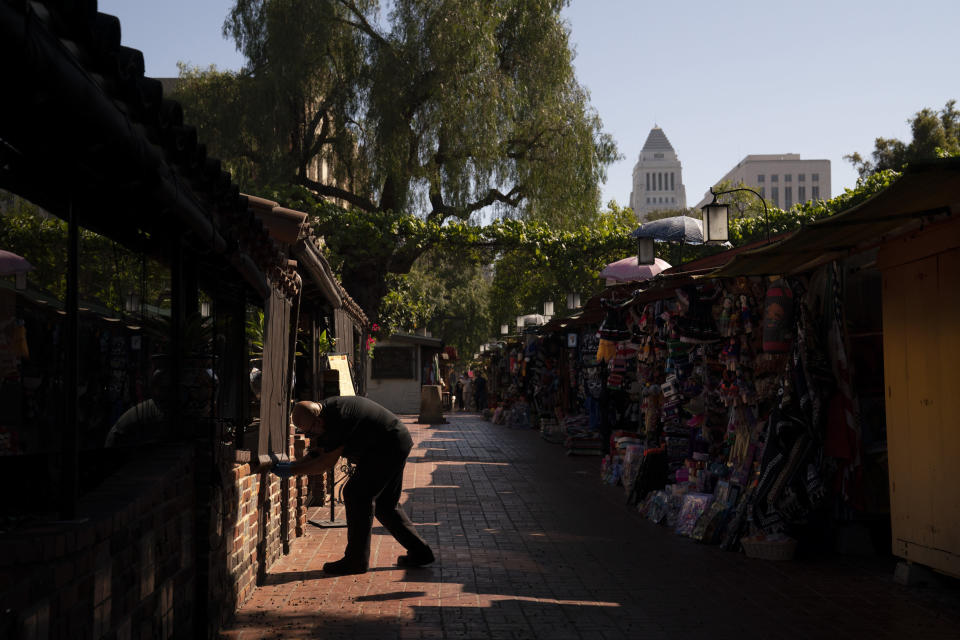 Peter Alamillo, one of managers at El Paseo Inn Mexican restaurant on Olvera Street, pulls down a blind for customers in the patio area of the restaurant in Los Angeles, Friday, June 4, 2021. As Latinos in California have experienced disproportionately worse outcomes from COVID-19, so too has Olvera Street. The shops lining the narrow brick walkway rely heavily on participants at monthly cultural celebrations, downtown office workers dining out, school field trips and Dodger baseball fans loading up on Mexican food before or after games. But the coronavirus killed tourism, kept office workers and pupils at home, cancelled events and kept fans from sporting events. (AP Photo/Jae C. Hong)