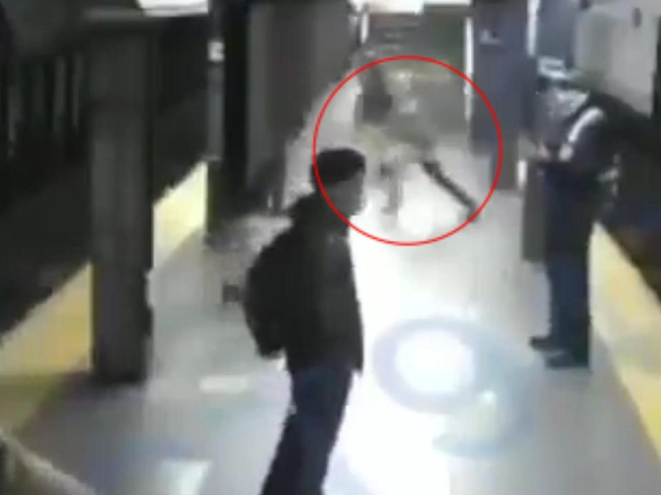 CCTV footage shows a man suddenly rushing forward to push a woman off a subway station platform onto the tracks as a train pulls into the station in New York (CCTV)